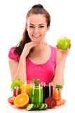Mujer joven con la variedad de zumos de la verdura y de fruta imagen de archivo