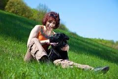 Mujer joven con Labrador negro Imagenes de archivo