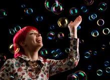 Mujer joven con las burbujas de jabón Foto de archivo