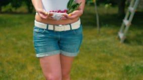 Mujer joven con las cerezas en camiseta que caminan descalzo en la hierba metrajes