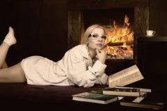 Mujer joven con las coletas en camisa del ` s del hombre sobre su cuerpo desnudo, leyendo un libro por la chimenea fotografía de archivo