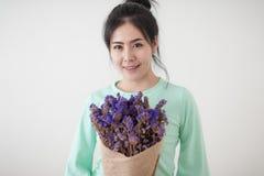 Mujer joven con las flores en su mano Imagenes de archivo