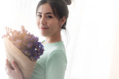 Mujer joven con las flores en su mano Fotos de archivo
