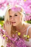 Mujer joven con las flores púrpuras Fotos de archivo