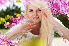 Mujer joven con las flores púrpuras Fotos de archivo libres de regalías