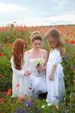 Mujer joven con las flores salvajes y las muchachas lindas en el spr floreciente Foto de archivo libre de regalías