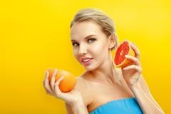 Mujer joven con las frutas en fondo anaranjado brillante Imagen de archivo