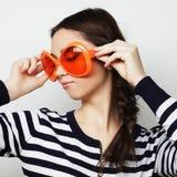 Mujer joven con las gafas de sol anaranjadas grandes Foto de archivo
