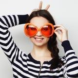 Mujer joven con las gafas de sol anaranjadas grandes Foto de archivo libre de regalías
