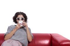 Mujer joven con las gafas de sol que bebe el café Imágenes de archivo libres de regalías
