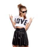 Mujer joven con las gafas de sol que dan la muestra del rock-and-roll Imágenes de archivo libres de regalías