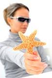 Mujer joven con las gafas de sol y las estrellas de mar Foto de archivo