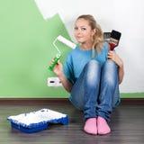 Mujer joven con las herramientas de la pintura Imagenes de archivo