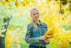 Mujer joven con las hojas de otoño Imagenes de archivo