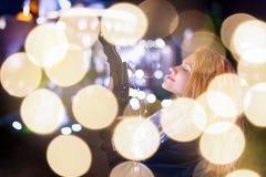 Mujer joven con las luces de hadas en noche fría de la ciudad que sueña alrededor imagen de archivo