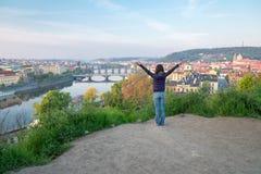 Mujer joven con las manos para arriba en la colina sobre el río y el brid de Moldava Fotos de archivo libres de regalías