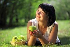 Mujer joven con las manzanas en hierba Imagen de archivo