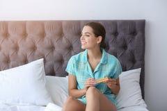 Mujer joven con las píldoras anticonceptivas en dormitorio fotos de archivo libres de regalías