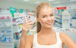 Mujer joven con las píldoras en droguería o farmacia Foto de archivo