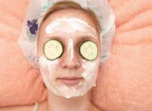 Mujer joven con las rebanadas del pepino en la cara en un salón del balneario Imagen de archivo libre de regalías