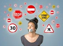 Mujer joven con las señales pegadas de la boca y de tráfico Imagenes de archivo