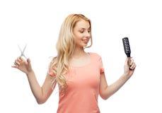Mujer joven con las tijeras y el cepillo para el pelo Imágenes de archivo libres de regalías