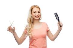 Mujer joven con las tijeras y el cepillo para el pelo Fotos de archivo libres de regalías