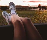 Mujer joven con las zapatillas de deporte con los pies apoyados en la ventanilla del coche en la puesta del sol foto de archivo