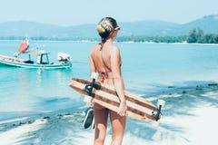 Mujer joven con longboard a disposición que camina en la arena blanca Imagenes de archivo