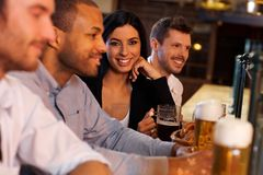 Mujer joven con los amigos en pub Foto de archivo libre de regalías
