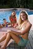 Mujer joven con los amigos por la piscina Imágenes de archivo libres de regalías
