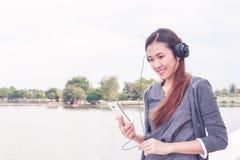 Mujer joven con los auriculares afuera Fotos de archivo libres de regalías