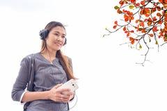 Mujer joven con los auriculares afuera Fotografía de archivo