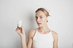 Mujer joven con los auriculares blancos y la luz eléctrica con el fondo vacío Fotos de archivo