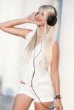 Mujer joven con los auriculares Disfrute de la música Fotografía de archivo