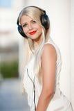 Mujer joven con los auriculares Disfrute de la música Fotos de archivo
