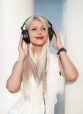 Mujer joven con los auriculares Disfrute de la música Imagen de archivo libre de regalías