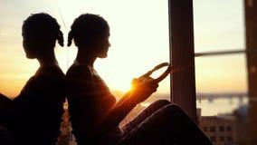 Mujer joven con los auriculares en el fondo de la puesta del sol de la ciudad Fotografía de archivo libre de regalías
