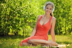 Mujer joven con los auriculares en hierba verde en el parque Fotos de archivo libres de regalías