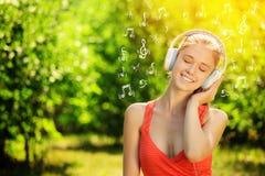 Mujer joven con los auriculares en hierba verde en el parque Imagenes de archivo