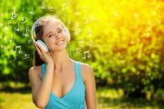 Mujer joven con los auriculares en hierba verde en el parque Imágenes de archivo libres de regalías