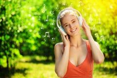 Mujer joven con los auriculares en hierba verde en el parque Fotografía de archivo