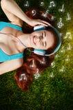 Mujer joven con los auriculares en hierba verde en el parque, música, infographic Foto de archivo