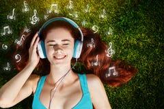 Mujer joven con los auriculares en hierba verde en el parque, música, infographic Fotos de archivo libres de regalías