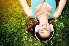 Mujer joven con los auriculares en hierba verde en el parque, música, infographic Foto de archivo libre de regalías