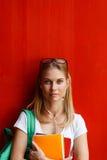 Mujer joven con los auriculares en la pared del rojo del espacio en blanco del fondo Foto de archivo