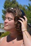 Mujer joven con los auriculares inal?mbricos, escuchando la m?sica en el jard?n foto de archivo libre de regalías