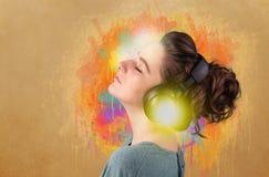 Mujer joven con los auriculares que escucha la música Foto de archivo