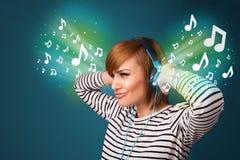 Mujer joven con los auriculares que escucha la música Imagen de archivo libre de regalías