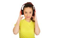 Mujer joven con los auriculares que escucha la música Fotografía de archivo
